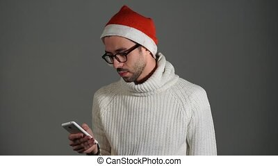 Serious brutal man in glasses and a red cap of Santa Claus calling by phone and is angry that no dials