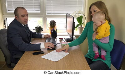 clerk officer in suit and client woman with newborn child....