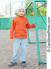 Little boy standing at goal