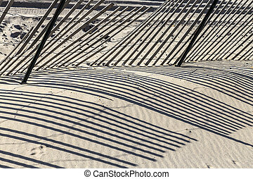 fence at the beach gives a harmonic shadow in morning light
