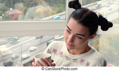 Charming young woman sitting near window and drink coffee -...