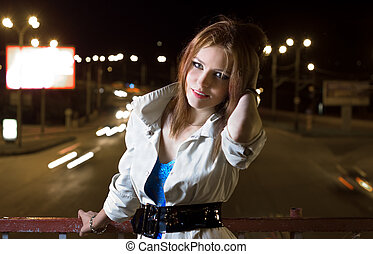 Beautiful young woman standing on illuminated street at...