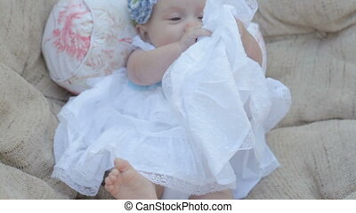 little baby girl sitting in white dress in chair.