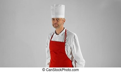 Handsome adult chef turns, he crosses his arms with knives and nods his head on a gray background