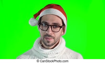 Handsome young man in stylish glasses and a hat of Santa Claus smiling at the camera on a green background