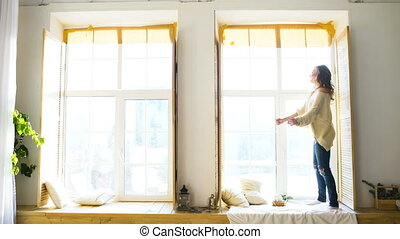 Young woman dancing on window in bedroom at sunny day