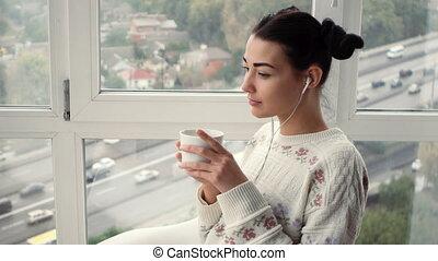 Charming young woman in earphones sitting near window...