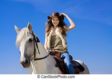 young cowgirl on white horse smile