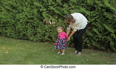 mom plays with a little girl in the Park - mom plays with a...