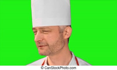 Handsome chef turns head, smiling at the camera and turns back on a green background