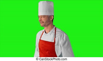 Handsome adult chef gives the thumbs-up to the camera and smile on a green background