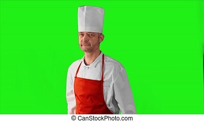 Handsome adult chef turns, he crosses his arms and nods his head on a green background