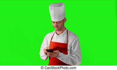 Handsome adult chef typing on smartphone, then he looking at the camera and smiling on a gray background