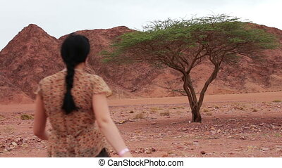 Young woman found the green tree in the desert