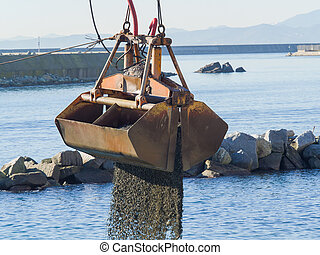 Dredge Clamshell Bucket unloading gravel in the water of a port