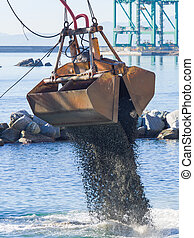 Dredge Clamshell Bucket unloading gravel in the water of a...