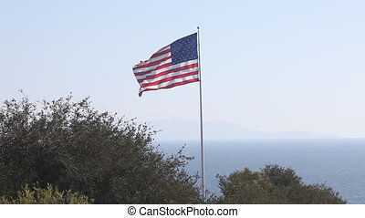 The United States of America flag flying high against a cloudy blue sky.