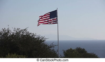 American and USA flag waving in front of blue sky - American...