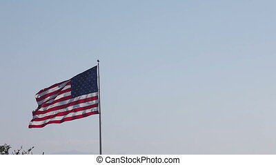 American and USA flag Union waving in front of blue cloudy...