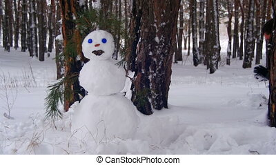Man in the Pine Forest Sculpts Snowman - Man in the pine...