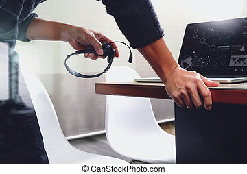 Man using VOIP headset with digital tablet computer docking...