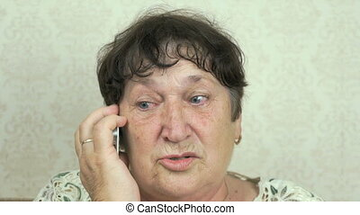 Senior woman holding smartphone talk to doctor at home