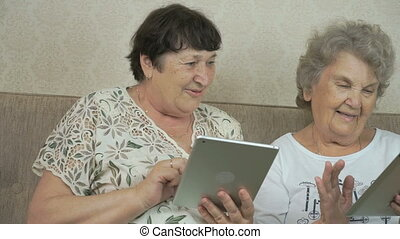 Two old women holding the silver digital tablets - Two old...