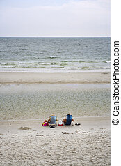 Sitting Beachside, Gulf Coast - A pair of beach-goers sit at...