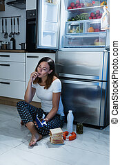 Woman Eating Chocolate In Kitchen