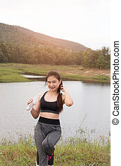 sport and health lifestyle - young woman with bottle of...