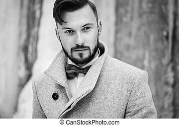 Outdoor portrait of handsome man in gray coat. Fashion...