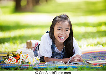 Happy asian girl sitting on grass and read a magazine book