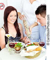 Loving young couple dining at the restaurant with waiter...
