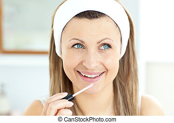 Charming woman applying gloss on her lips in the bathroom