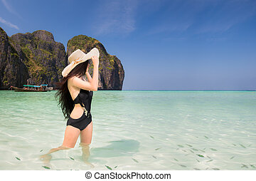 Portrait of woman in black swim posing on tropical beach,...