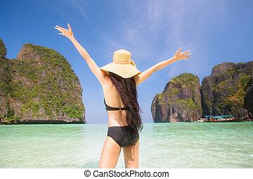 Portrait of woman in black swim posing on tropical beach,...