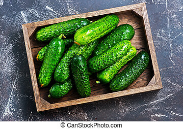 cucumbers in box and on a table