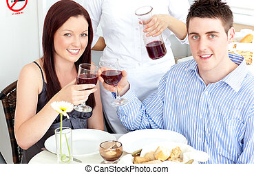 Lovely young couple dining at the restaurant with waiter...