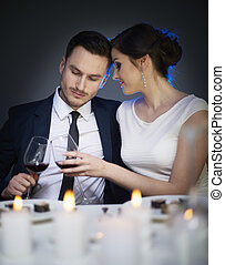 Couple clinking red wine glasses at table