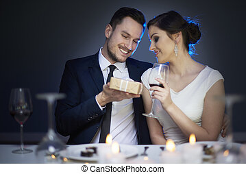 Young couple with present and glass of red wine