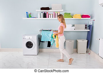 Woman Walking With Clothes In Utility Room - Happy Woman...