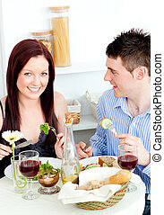 Smiling young couple dining in the kitchen at home