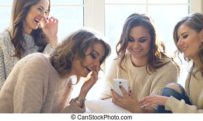 four beautiful girls discuss smile sitting on window. Girlfriends having fun and laugh in bedroom