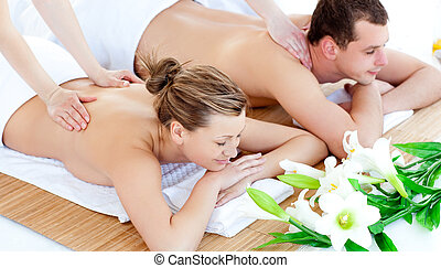Enamored young couple enjoying a back massage in a spa...