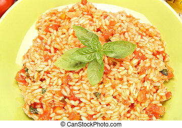 Risotto with tomatoes on a green plate decorated with basil...
