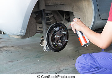 mechanic spray chemical to clean brake during tyre...