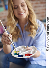 Dipping painting brush in the color