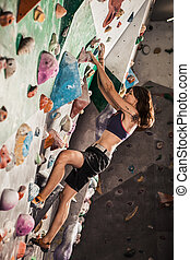 woman bouldering in climbing gym - Young woman bouldering in...