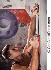 Muscular man practicing rock-climbing