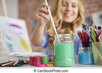 Woman dipping paintbrush in bottle